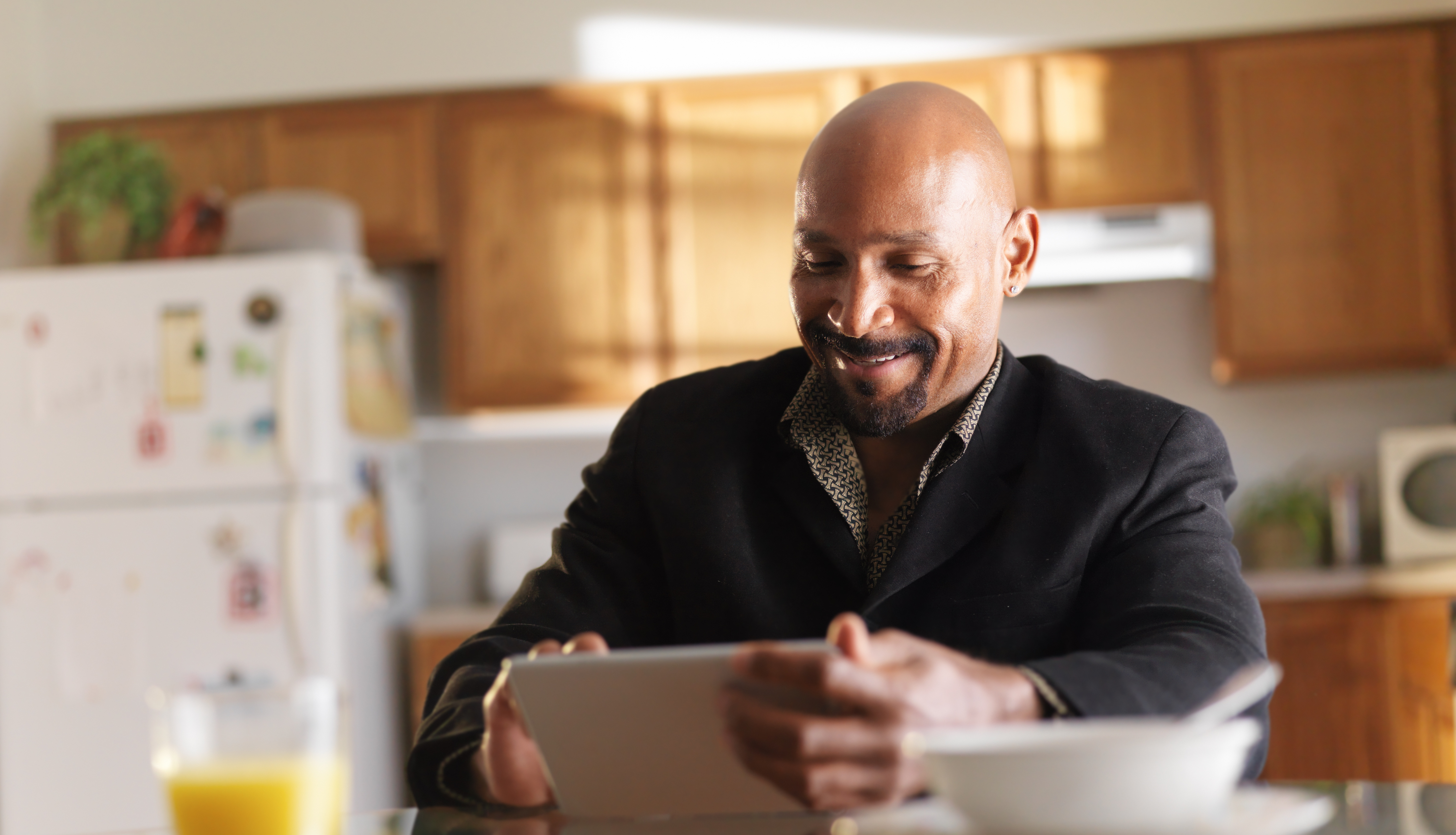 middle aged man in kitchen on tablet