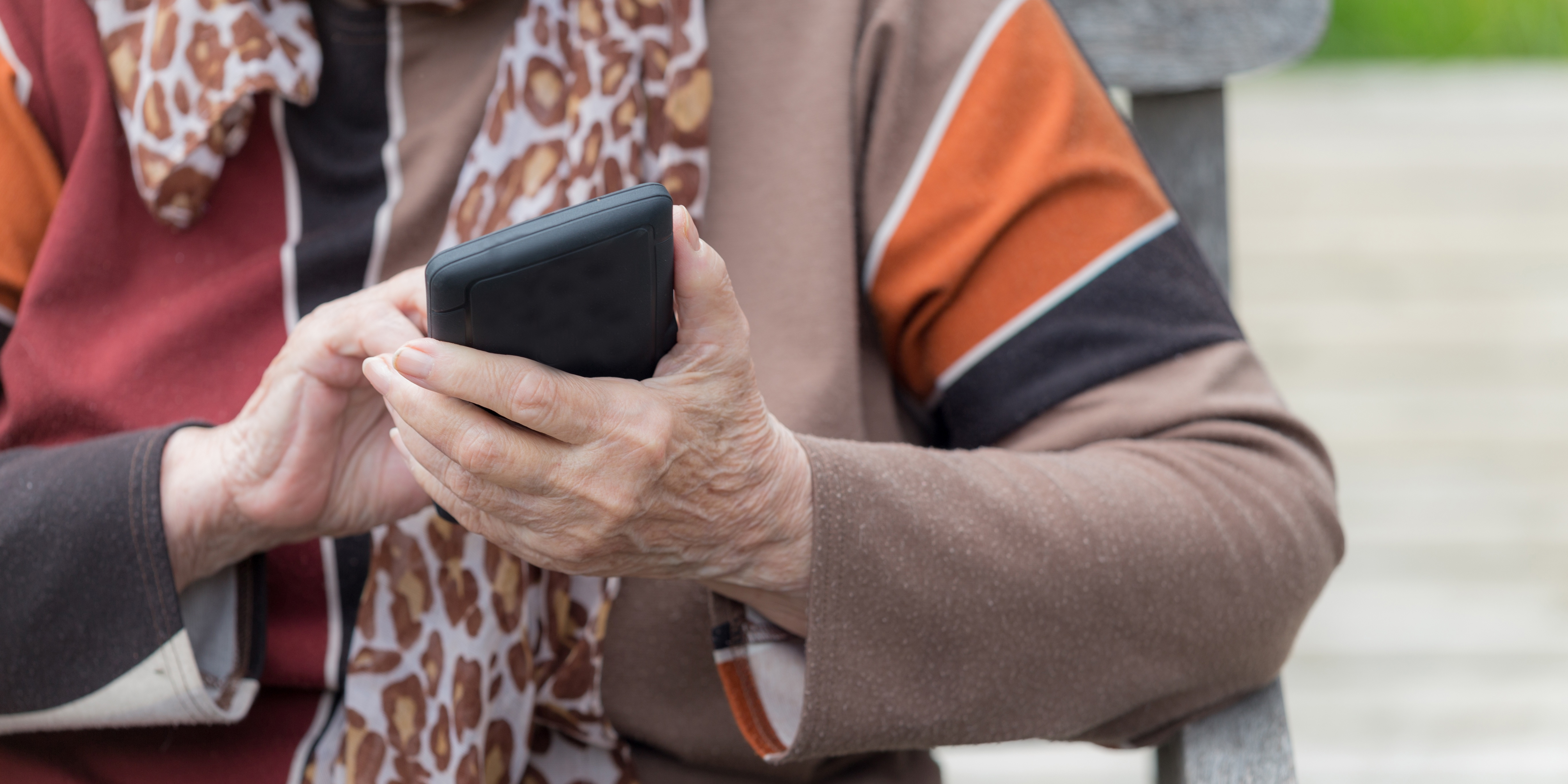 older woman hand with phone